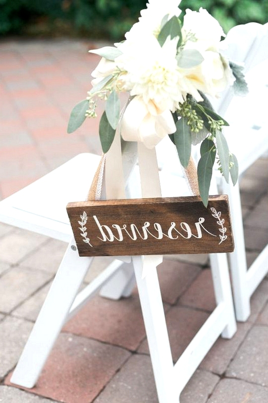 Rustic wooden reserved sign for wedding ceremony