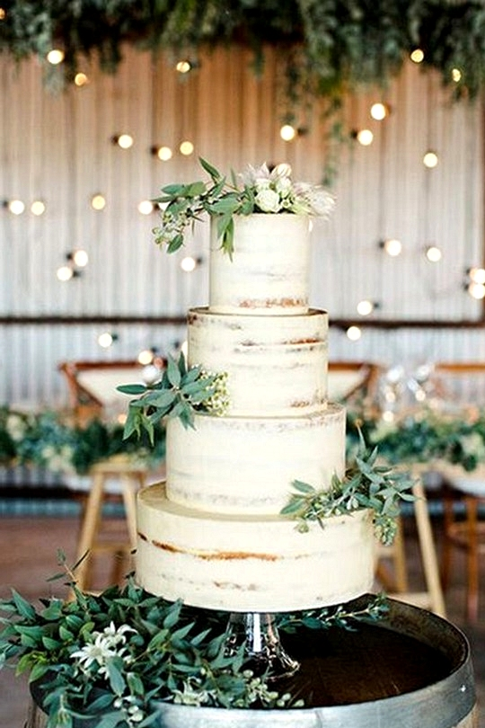 green and white wedding cake on a wine barrel