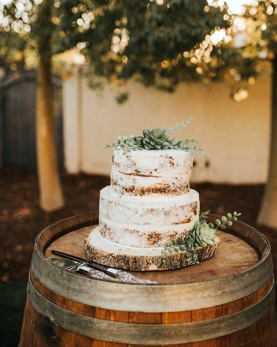 semi naked wedding cakes topped with greens on a wine barrel