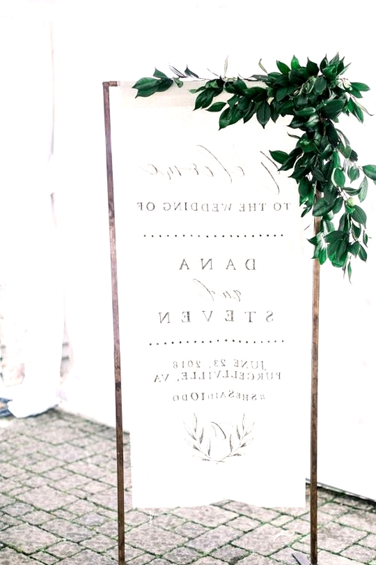 fabirc wedding welcome sign with greenery
