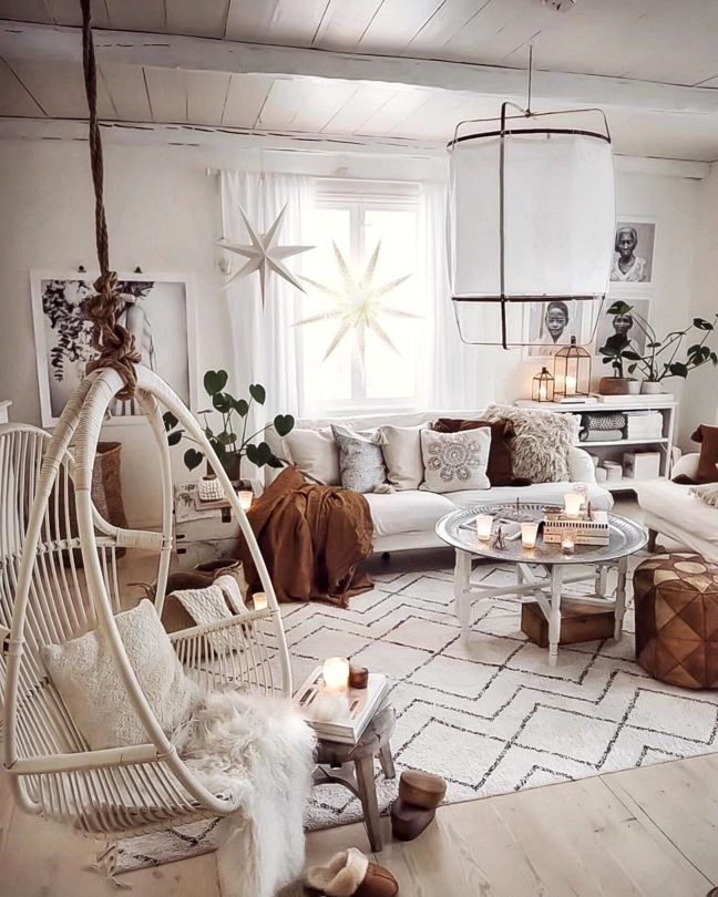 Scandinavian Bohemian white living room with white hanging rattan chair and brown Moroccan Round Leather Pouf